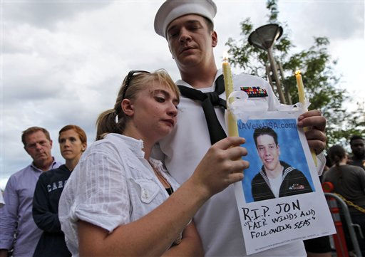 U.S. Navy Petty Officer Second Class Keith Hoover, right, with his girlfriend Monica Matryba hold a photo of fellow sailor Jon Larimer at the Aurora Municipal Center, Sunday, July 22, 2012, in Aurora, Colo., during a prayer vigil for the victims of Friday&#39;s mass shooting at a movie theater. Twelve people were killed and dozens were injured in a shooting attack early Friday at the packed theater during a showing of the Batman movie, &#34;The Dark Knight Rises.&#34; Police have identified the suspected shooter as James Holmes, 24. &#40;AP Photo&#47;Alex Brandon&#41; <span class=meta>(AP Photo&#47; Alex Brandon)</span>