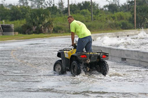 Brandon Ellis of Waveland takes advantage of the height of his ATV to ride up to the waves coming over the seawall alongside Beach Boulevard in Waveland, Miss., as Isaac&#39;s winds begin to hit the Mississippi Gulf Coast, Tuesday, Aug. 28, 2012.   <span class=meta>(AP Photo&#47; Rogelio V. Solis)</span>
