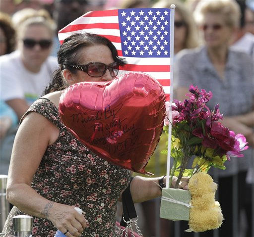 A woman carries a balloon that says &#34;Missed by many, forgotten by none,&#34; as she walks to a memorial display, Sunday, July 22, 2012, in Aurora, Colo., during a prayer vigil for the victims of Friday&#39;s mass shooting at a movie theater. Twelve people were killed and dozens were injured in a shooting attack early Friday at the packed theater during a showing of the Batman movie, &#34;The Dark Knight Rises.&#34; Police have identified the suspected shooter as James Holmes, 24. &#40;AP Photo&#47;Ted S. Warren&#41; <span class=meta>(AP Photo&#47; Ted S. Warren)</span>