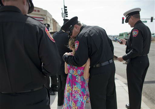 Anaheim, Calif. firefighter Brent Hirst, center, kisses his daughter, Morgan, 9, on the head while waiting to enter Tim&#39;s Toyota Center for a memorial service, Tuesday, July 9, 2013 in Prescott, Ariz. Thousands of firefighters from around the nation arrived to attend a memorial service for Prescott&#39;s Granite Mountain Hotshots to pay final respects on Tuesday at the minor league hockey arena in Prescott Valley, not far from where they died Sunday, June 30. Nineteen members of the crew were overrun by smoke and fire while battling a blaze on a ridge in Yarnell, about 80 miles northwest of Phoenix.    <span class=meta>(AP Photo&#47; Julie Jacobson)</span>