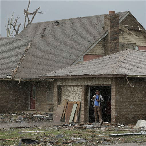 An unidentified man watches a rain storm from inside the garage of his tornado-damaged home Tuesday, May 21, 2013, in Moore, Okla. A huge tornado roared through the Oklahoma City suburb Monday, flattening entire neighborhoods and destroying an elementary school with a direct blow as children and teachers huddled against winds.   <span class=meta>(AP Photo&#47; Charlie Riedel)</span>