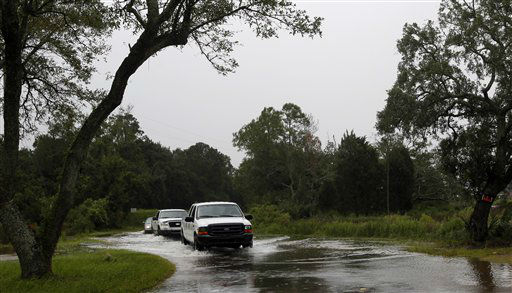 Vehicles drive through a flooded  Shell Belt Road in Bayou La Batre, Ala. on Tuesday, Aug.  28, 2012.  The U.S. National Hurricane Center in Miami said Isaac became a Category 1 hurricane Tuesday with winds of 75 mph. It could get stronger by the time it&#39;s expected to reach the swampy coast of southeast Louisiana.  <span class=meta>(AP Photo&#47; Butch Dill)</span>