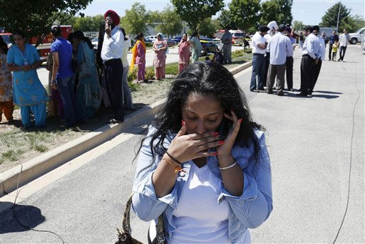 A woman reacts with others as they await word on a shooting at a Sikh temple in Oak Creek, Wis., Sunday, Aug. 5, 2012, where police and witnesses describe a chaotic situation with an unknown number of victims, suspects and possible hostages.   <span class=meta>(AP Photo&#47; Jeffrey Phelps)</span>