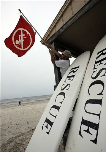 Lifeguard Duane Gonzalez takes down the red warning flag on a beach in Tampa, Fla., Sunday, Aug. 26, 2012.  Some rain and winds from Tropical Storm Isaac are beginning to reach Tampa where the Republican National Convention has postponed the start of their meeting because of the approaching storm.  <span class=meta>(AP Photo&#47; Dave Martin)</span>