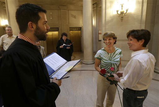 "<div class=""meta image-caption""><div class=""origin-logo origin-image ""><span></span></div><span class=""caption-text"">Marriage commissioner Jared Scherer, left, officiates as Pam Shaheen, center, marries Mary Beth Gabriel at City Hall in San Francisco, Friday, June 28, 2013. A three-judge panel of the 9th U.S. Circuit Court of Appeals issued a brief order Friday afternoon dissolving, ""effective immediately,"" a stay it imposed on gay marriages while the lawsuit challenging the ban advanced through the courts.  (AP Photo/ Jeff Chiu)</span></div>"