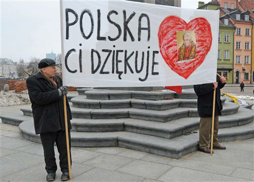 Two men stand with a banner reading &#34;Poland Thanks You&#34; on the Zamkowy Square in Warsaw, Poland, Thursday, Feb. 28, 2013, on the final day of Pope Benedict XVI&#39;s papacy. At 8 p.m. Benedict will become the first pontiff in 600 years to resign.  <span class=meta>(AP photo)</span>