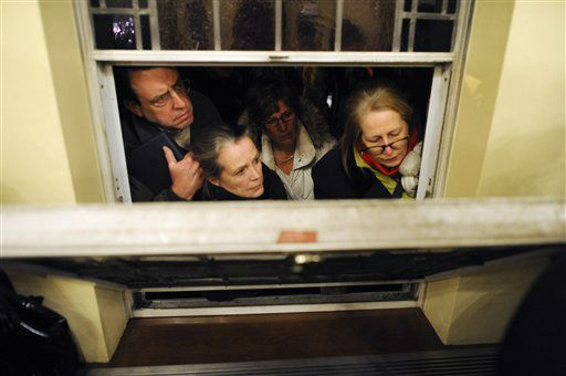 Mourners look in from outside during a vigil service for victims of the Sandy Hook Elementary School shooting, at the St. Rose of Lima Roman Catholic Church in Newtown, Conn. Friday, Dec. 14, 2012. A man killed his mother at their home and then opened fire Friday inside the elementary school where she taught, massacring 26 people, including 20 children, as youngsters cowered in fear to the sound of gunshots reverberating through the building and screams echoing over the intercom (AP Photo/Andrew Gombert, Pool)