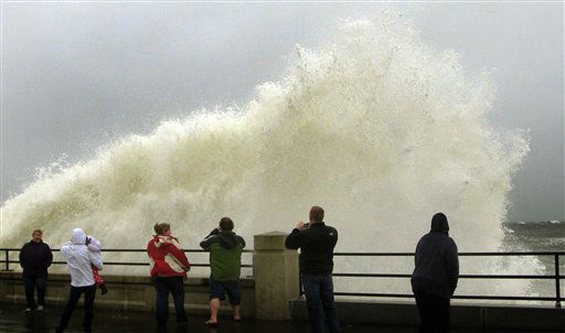 "<div class=""meta ""><span class=""caption-text "">Peaople watch waves crash in Hampton, N.H., from the effects of Hurricane Sandy Monday, Oct. 29, 2012. The hurricane continued on its path Monday, as the storm forced the shutdown of mass transit, schools and financial markets, sending coastal residents fleeing, and threatening a dangerous mix of high winds and soaking rain.   (AP Photo/ Jim Cole)</span></div>"