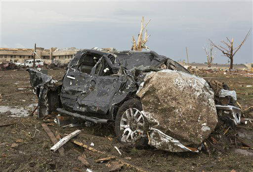 "<div class=""meta ""><span class=""caption-text "">A truck lays damaged in a field near the Moore Medical Center, background, after a tornado moves through Moore, Okla. on Monday, May 20, 2013.   (AP Photo/ Alonzo Adams)</span></div>"