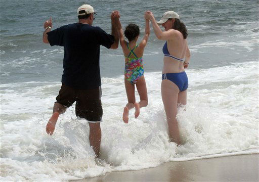 Daniel Sobel, of New City, N.Y., left, and his sister Joanna Sobel, right, lift his 8-year-old daughter Rachel over a wave as it comes crashing ashore in Point Pleasant Beach, N.J., Monday, Aug. 27, 2012. The effects of Tropical Storm Isaac, more than 1,100 miles away, have been roiling the surf at the Jersey Shore, restricting swimming and keeping lifeguards on their toes.  <span class=meta>(AP Photo&#47; Wayne Parry)</span>