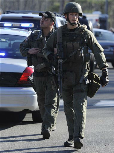 Law enforcement personnel walk down the street from the scene of a shooting at the Sandy Hook Elementary School in Newtown, Conn., about 60 miles &#40;96 kilometers&#41; northeast of New York City, Friday, Dec. 14, 2012.  A man opened fire Friday inside two classrooms at the school where his mother worked as a teacher, killing 26 people, including 20 children.  The killer, armed with two handguns, committed suicide at the school and another person was found dead at a second scene, bringing the toll to 28, authorities said. A law enforcement official identified the gunman as 20-year-old Adam Lanza.    <span class=meta>(AP Photo&#47; Jessica Hill)</span>