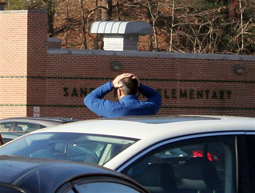 In this photo provided by the Newtown Bee, a man stands with his hands on his head outside of Sandy Hook Elementary School in Newtown, Conn., where authorities say a gunman opened fire, killing 26 people, including 20 children, Friday, Dec. 14, 2012. &#40;AP Photo&#47;Newtown Bee, Shannon Hicks&#41;   <span class=meta>(AP Photo&#47; Shannon Hicks)</span>