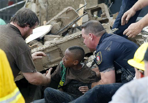 A boy is pulled from beneath a collapsed wall at the Plaza Towers Elementary School following a tornado in Moore, Okla., Monday, May 20, 2013. A tornado as much as a mile &#40;1.6 kilometers&#41; wide with winds up to 200 mph &#40;320 kph&#41; roared through the Oklahoma City suburbs Monday, flattening entire neighborhoods, setting buildings on fire and landing a direct blow on an elementary school. &#40;AP Photo&#47; Sue Ogrocki&#41; <span class=meta>(AP Photo&#47; Sue Ogrocki)</span>