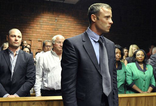Olympian Oscar Pistorius, foreground, stands following his bail hearing, as his brother Carl, left, and father Henke, second from left, look on in Pretoria, South Africa, Tuesday, Feb. 19, 2013. Pistorius fired into the door of a small bathroom where his girlfriend was cowering after a shouting match on Valentine&#39;s Day, hitting her three times, a South African prosecutor said Tuesday as he charged the sports icon with premeditated murder. The magistrate ruled that Pistorius faces the harshest bail requirements available in South African law. He did not elaborate before a break was called in the session.   <span class=meta>(AP Photo&#47; Uncredited)</span>