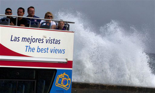 "<div class=""meta ""><span class=""caption-text "">Tourists sit on a bus as they tour the city as a wave crashes against the Malecon in Havana, Cuba, Thursday, Oct. 25, 2012. Hurricane Sandy blasted across eastern Cuba on Thursday as a potent Category 2 storm and headed for the Bahamas after causing at least two deaths in the Caribbean.   (AP Photo/ Ramon Espinosa)</span></div>"