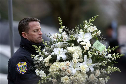 A police officer carries flowers into a funeral service for 6-year-old Noah Pozner, Monday, Dec. 17, 2012, in Fairfield, Conn. Pozner was killed when a gunman walked into Sandy Hook Elementary School in Newtown Friday and opened fire, killing 26 people, including 20 children. &#40;AP Photo&#47;Jason DeCrow&#41; <span class=meta>(AP Photo&#47; Jason DeCrow)</span>