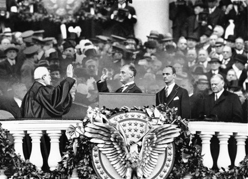President Franklin D. Roosevelt takes the oath of office from Chief Justice Charles E. Hughes at the inauguration, March 4, 1933. At right is Herbert Hoover and behind the president is his eldest son James Roosevelt. &#40;AP Photo&#41; <span class=meta>(AP Photo&#47; Uncredited)</span>