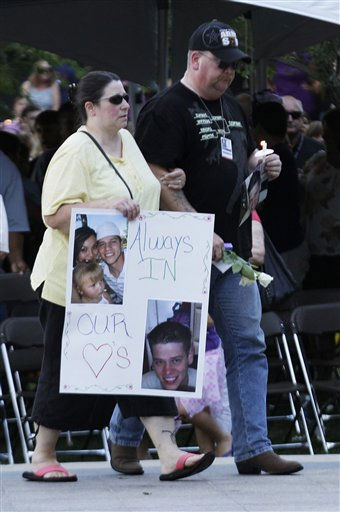 Family members of Jonathan Blunk carry a poster with his photo on it, Sunday, July 22, 2012, in Aurora, Colo., at a prayer vigil for the victims of Friday&#39;s mass shooting at a movie theater. &#40;AP Photo&#47;Ted S. Warren&#41; <span class=meta>(AP Photo&#47; Ted S. Warren)</span>