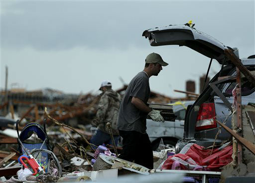 Justin Stehan salvages photographs from his tornado-ravaged home Tuesday, May 21, 2013, in Moore, Okla. A huge tornado roared through the Oklahoma City suburb Monday, flattening entire neighborhoods and destroying an elementary school with a direct blow as children and teachers huddled against winds.   <span class=meta>(AP Photo&#47; Charlie Riedel)</span>