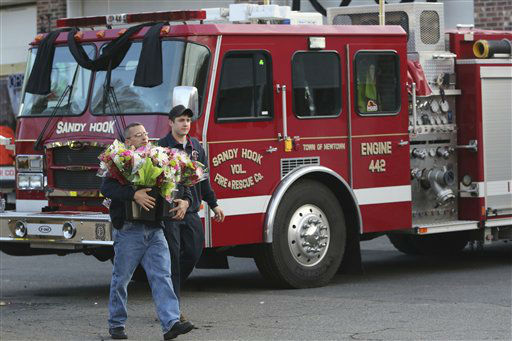 A couple of volunteer firefighters carry flowers past their fire truck they will place at a makeshift memorial at a sign for the Sandy Hook Elementary school,  Saturday, Dec. 15, 2012 in Sandy Hook village of Newtown, Conn.  The massacre of 26 children and adults at Sandy Hook Elementary school elicited horror and soul-searching around the world even as it raised more basic questions about why the gunman, 20-year-old Adam Lanza, would have been driven to such a crime and how he chose his victims.  <span class=meta>(AP Photo&#47; Mary Altaffer)</span>