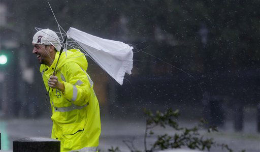 A man holds a broken umbrella in the wind as Hurricane Isaac makes landfall, Wednesday, Aug. 29, 2012, in New Orleans, La.  Isaac was packing 80 mph winds, making it a Category 1 hurricane. It came ashore early Tuesday near the mouth of the Mississippi River, driving a wall of water nearly 11 feet high inland and soaking a neck of land that stretches into the Gulf.   <span class=meta>(AP Photo&#47; Eric Gay)</span>