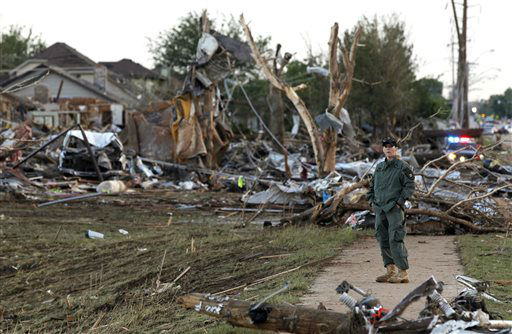 A member of a security team helps guard an area of rubble from a destroyed residential neighborhood, one day after a tornado moved through Moore, Okla., Tuesday, May 21, 2013. The huge tornado roared through the Oklahoma City suburb Monday, flattening entire neighborhoods and destroying an elementary school with a direct blow as children and teachers huddled against the winds. &#40;AP Photo&#47;Brennan Linsley&#41;  <span class=meta>(AP Photo&#47; Brennan Linsley)</span>