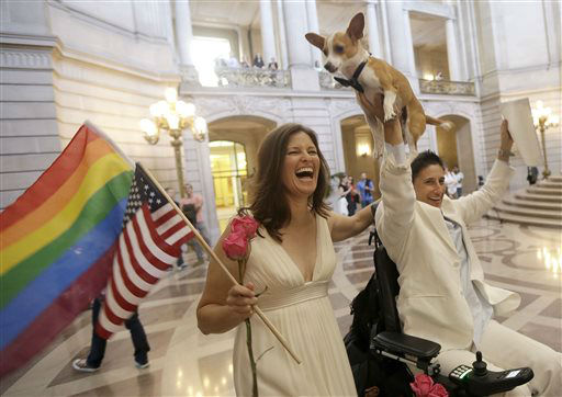 Jen Rainin, left, laughs as her wife Frances holds up their dog Punum after they were married at City Hall in San Francisco, Friday, June 28, 2013. A three-judge panel of the 9th U.S. Circuit Court of Appeals issued a brief order Friday afternoon dissolving, &#34;effective immediately,&#34; a stay it imposed on gay marriages while the lawsuit challenging the ban advanced through the courts.  <span class=meta>(AP Photo&#47; Jeff Chiu)</span>