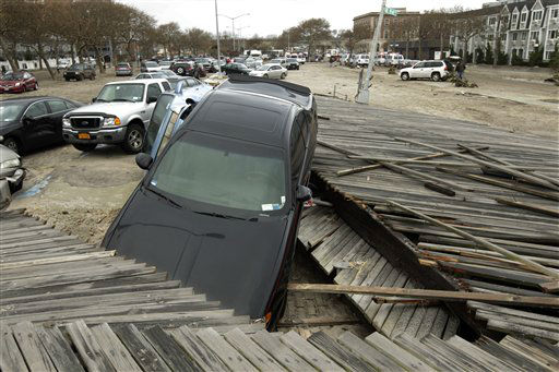 Pedestrians walk past the boardwalk and cars displaced by superstorm Sandy, near Rockaway Beach in the New York City borough of Queens, Tuesday, Oct. 30, 2012, in New York. Sandy, the storm that made landfall Monday, caused multiple fatalities, halted mass transit and cut power to more than 6 million homes and businesses.   <span class=meta>(AP Photo&#47; Frank Franklin II)</span>