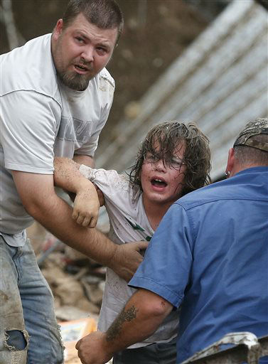 A child calls to his father after being pulled from the rubble of the Tower Plaza Elementary School following a tornado in Moore, Okla., Monday, May 20, 2013. A tornado as much as a mile &#40;1.6 kilometers&#41; wide with winds up to 200 mph &#40;320 kph&#41; roared through the Oklahoma City suburbs Monday, flattening entire neighborhoods, setting buildings on fire and landing a direct blow on an elementary school. &#40;AP Photo Sue Ogrocki&#41; <span class=meta>(AP Photo&#47; Sue Ogrocki)</span>