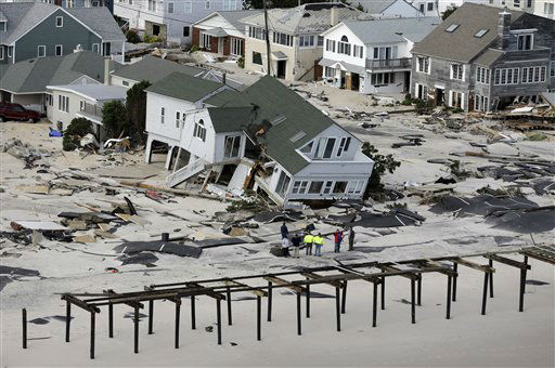 "<div class=""meta ""><span class=""caption-text "">In this aerial photo, people survey destruction left in the wake of superstorm Sandy, Wednesday, Oct. 31, 2012, in Seaside Heights, N.J.   (AP Photo/ Mike Groll)</span></div>"