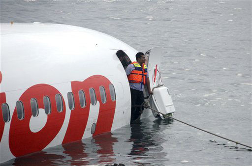 In this photo released by Indonesian Police, a rescue worker stands at the doorway of a crashed Lion Air plane on the water near the airport in Bali, Indonesia on Saturday, April 13, 2013. The plane carrying more than 100 passengers and crew overshot a runway on the Indonesian resort island of Bali on Saturday and crashed into the sea, injuring nearly two dozen people, officials said.   <span class=meta>(AP Photo&#47; Handout Indonesian Police)</span>