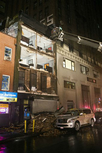 The facade of a four-story building on 14th Street and 8th Avenue collapsed onto the sidewalk, Monday, Oct. 29, 2012, in New York. Hurricane Sandy bore down on the Eastern Seaboard&#39;s largest cities Monday, forcing the shutdown of mass transit, schools and financial markets, sending coastal residents fleeing, and threatening a dangerous mix of high winds, soaking rain and a surging wall of water up to 11 feet tall. &#40;AP Photo&#47; John Minchillo&#41; <span class=meta>(AP Photo&#47; John Minchillo)</span>