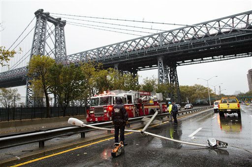 Police and firefighters respond to a downed street light on FDR drive, Monday, Oct. 29, 2012, in New York. Hurricane Sandy continued on its path Monday, forcing the shutdown of mass transit, schools and financial markets, sending coastal residents fleeing, and threatening a dangerous mix of high winds and soaking rain.  &#40;AP Photo&#47;John Minchillo&#41; <span class=meta>(AP Photo&#47; John Minchillo)</span>