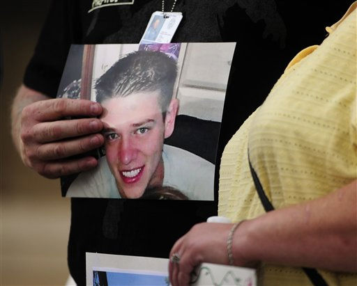 A family member holds a picture of Jonny Blunk Sunday, July 22, 2012, in Aurora, Colo., at a prayer vigil for the victims of Friday&#39;s mass shooting at a movie theater. 12 people were killed and 58 were injured in a shooting during an early Friday premiere of ?The Dark Knight Rises.&#34; &#40;AP Photo&#47;The Denver Post, AAron Ontiveroz, Pool&#41; <span class=meta>(AP Photo&#47; AAron Ontiveroz)</span>