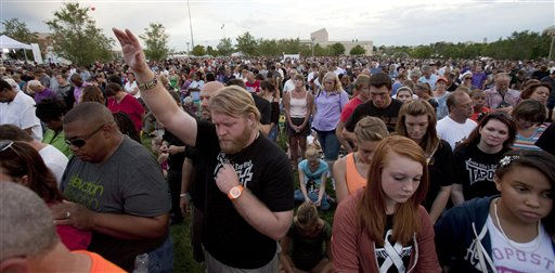 "<div class=""meta ""><span class=""caption-text "">Justin Wren, 25, who recently moved from Aurora, joins thousands of people during a prayer vigil held to remember the lost and injured in Friday's mass shooting rampage at a movie theater, in a park outside the Aurora Municipal Center in Aurora, Colo., Sunday, July 22, 2012. Twelve people were killed and dozens were injured in a shooting attack early Friday at the packed theater during a showing of the Batman movie, ""The Dark Knight Rises."" Police have identified the suspected shooter as James Holmes, 24.  (AP Photo/Barry Gutierrez) (AP Photo/ Barry Gutierrez)</span></div>"