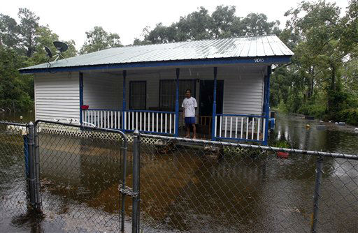 Han Ho stands on his front porch as flood water surrounds his home in Bayou La Batre on Wednesday, Aug. 29, 2012.  Hurricane Isaac has dumped more than five inches of rain on the Alabama coast and knocked out power to some residents, but it hasn&#39;t interrupted the everyday life of others.  Residents of Dauphin Island lost power, but they also escaped the worst of Isaac. The weather service reports wind gusts of 47 mph.   <span class=meta>(AP Photo&#47; Butch Dill)</span>