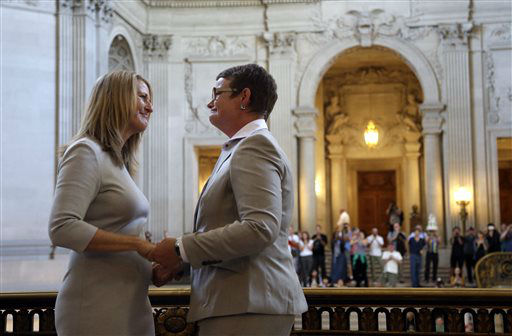 Sandy Stier, left, exchanges wedding vows with Kris Perry during a ceremony presided by California Attorney General Kamala Harris at City Hall in San Francisco, Friday,  June 28, 2013. Stier and Perry, the lead plaintiffs in the U.S. Supreme Court case that overturned California&#39;s same-sex marriage ban, tied the knot about an hour after a federal appeals court freed same-sex couples to obtain marriage licenses for the first time in 4 1&#47;2 years.  <span class=meta>(AP Photo&#47; Marcio Jose Sanchez)</span>