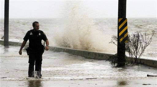 Officer Ted Johnson inspects a road along Mobile Bay as waves crash over the sea wall from Hurricane Isaac&#39;s storm surge in Mobile, Ala. on Wednesday, Aug. 29, 2012.  Hurricane Isaac has dumped more than five inches of rain on the Alabama coast and knocked out power to some residents, but it hasn&#39;t interrupted the everyday life of others.  Residents of Dauphin Island lost power, but they also escaped the worst of Isaac. The weather service reports wind gusts of 47 mph.  <span class=meta>(AP Photo&#47; Butch Dill)</span>