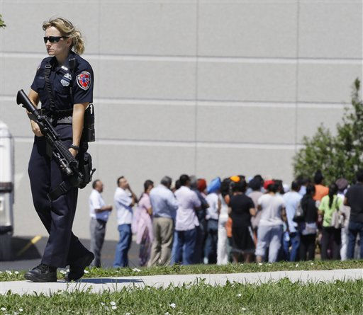 Police stand guard as bystanders watch at the scene of a shooting inside a Sikh temple in Oak Creek, Wis., Sunday, Aug. 5, 2012. Police and witnesses describe a chaotic situation with an unknown number of victims, suspects and possible hostages.   <span class=meta>(AP Photo&#47; Jeffrey Phelps)</span>