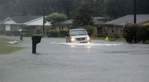 A motorist navigates through a flooded street, Wednesday, Aug. 29, 2012, in Gulfport, Miss. Isaac pelted parts of south Mississippi with heavy rains, flooding some homes in low-lying areas and turning parts of beachside U.S. Highway 90 into a river near Biloxi casinos.  <span class=meta>(AP Photo&#47; John Bazemore)</span>