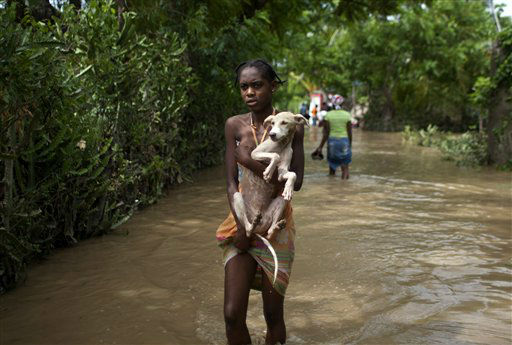 A young woman carries a dog on a flooded street after the passing of Tropical Storm Isaac in Port-au-Prince, Haiti, Sunday Aug. 26, 2012. The death toll in Haiti from Tropical Storm Isaac has climbed to seven after an initial report of four deaths, the Haitian government said Sunday.  <span class=meta>(AP Photo&#47; Dieu Nalio Chery)</span>