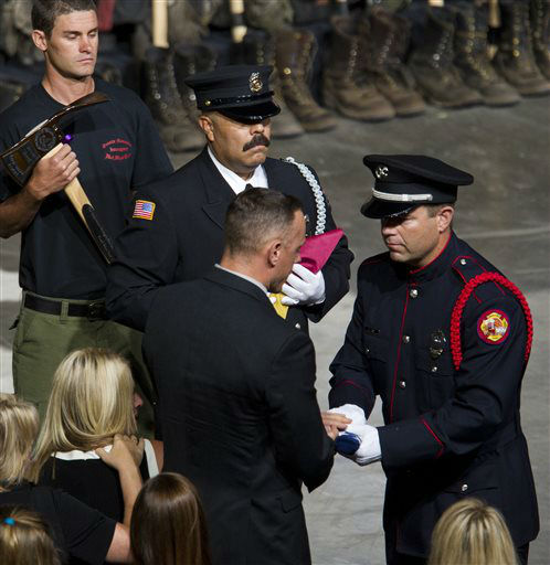"<div class=""meta ""><span class=""caption-text "">A flag is presented to the family of fallen firefighter Jesse Steed during a memorial service for the 19 fallen firefighters at Tim's Toyota Center in Prescott Valley, Ariz. on Tuesday, July 9, 2013.   Prescott's Granite Mountain Hotshots were overrun by smoke and fire while battling a blaze on a ridge in Yarnell, about 80 miles northwest of Phoenix on June 30, 2013.     (AP Photo/ MICHAEL CHOW)</span></div>"