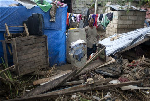 A woman stands among her belongings outside her damaged home after the passing of Tropical Storm Isaac in Port-au-Prince, Haiti, Sunday Aug. 26, 2012. The death toll in Haiti from Tropical Storm Isaac has climbed to seven after an initial report of four deaths, the Haitian government said Sunday.  <span class=meta>(AP Photo&#47; Dieu Nalio Chery)</span>