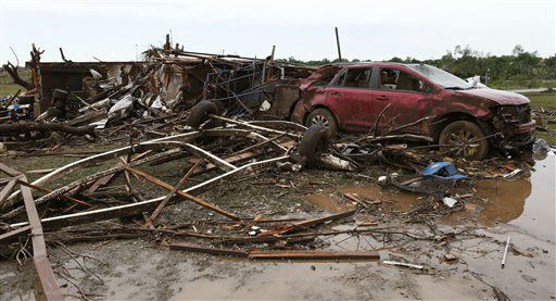 A a home and vehicle in Moore, Okla. sit severely damaged on Tuesday, May 21, 2013. A huge tornado roared through the Oklahoma City suburb Monday, flattening entire neighborhoods and destroying an elementary school with a direct blow as children and teachers huddled against winds.    <span class=meta>(AP Photo&#47; Alonzo Adams)</span>