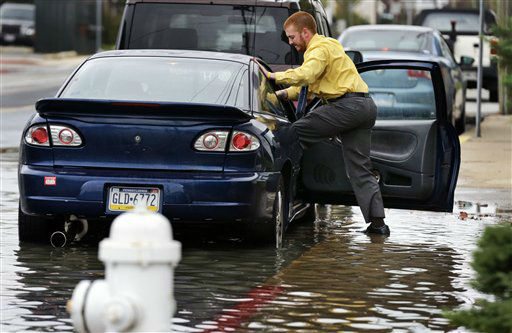Cody Billotte walks through the high water as he loads his car to go to work as Hurricane Sandy bears down on the East Coast, Sunday, Oct. 28, 2012, in Ocean City, Md.  Governors from North Carolina, where steady rains were whipped by gusting winds Saturday night, to Connecticut declared states of emergency. Delaware ordered mandatory evacuations for coastal communities by 8 p.m. Sunday. &#40;AP Photo&#47;Alex Brandon&#41; <span class=meta>(AP Photo&#47; Alex Brandon)</span>