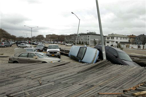 Pedestrians walk past the boardwalk and cars displaced by superstorm Sandy, near Rockaway Beach in the New York City borough of Queens Tuesday, Oct. 30, 2012, in New York. Sandy, the storm that made landfall Monday, caused multiple fatalities, halted mass transit and cut power to more than 6 million homes and businesses.   <span class=meta>(AP Photo&#47; Frank Franklin II)</span>