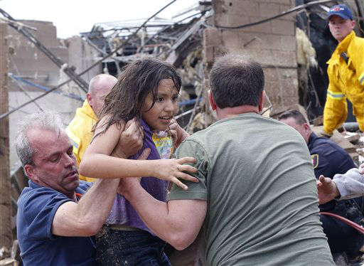 A child is pulled from the rubble of the Plaza Towers Elementary School in Moore, Okla., and passed along to rescuers Monday, May 20, 2013. A tornado as much as a mile &#40;1.6 kilometers&#41; wide with winds up to 200 mph &#40;320 kph&#41; roared through the Oklahoma City suburbs Monday, flattening entire neighborhoods, setting buildings on fire and landing a direct blow on an elementary school.&#40;AP Photo Sue Ogrocki&#41; <span class=meta>(AP Photo&#47; Sue Ogrocki)</span>