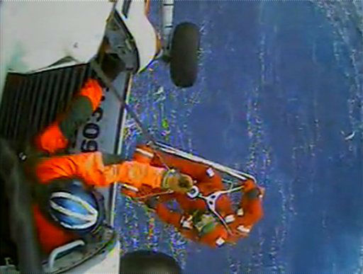 In this image made from video and released by the U.S. Coast Guard, a USCG crew member uses a hoist to bring up a survivor into a helicopter. A replica tall ship caught in Hurricane Sandy's wrath began taking on water, forcing the crew to abandon the boat Monday in rough seas off the North Carolina coast. The Coast Guard rescued 14 crew members by helicopter, but two people were still missing.