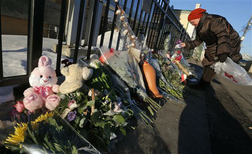 A Russian woman puts a toy near the U.S. Embassy in Moscow, Russia, Sunday, Dec. 16, 2012. The massacre of 26 children and adults at Sandy Hook Elementary school elicited horror and soul-searching around the world even as it raised more basic questions about why the gunman, 20-year-old Adam Lanza, would have been driven to such a crime and how he chose his victims. (AP Photo/Dmitry Lovetsky)
