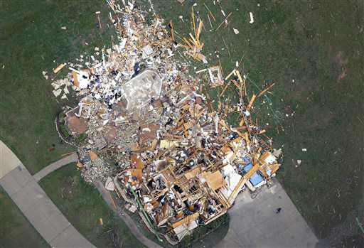 "<div class=""meta ""><span class=""caption-text "">In this aerial photo, a person, lower right, stand in front of a home demolished home by Monday's tornado, in Moore, Okla., Tuesday, May 21, 2013. The huge tornado roared through the Oklahoma City suburb Monday, flattening entire neighborhoods and destroying an elementary school with a direct blow as children and teachers huddled against winds.  (AP Photo/ Tony Gutierrez)</span></div>"
